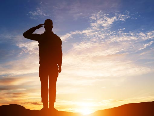 saluting soldier at sunset