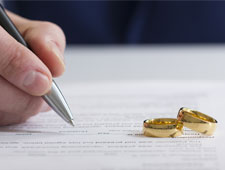 hand signing an agreement with wedding bands sitting on table