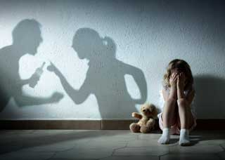 child on floor with teddybear with shadow of parents fighting in background
