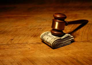 gavel on top of pile of cash on table